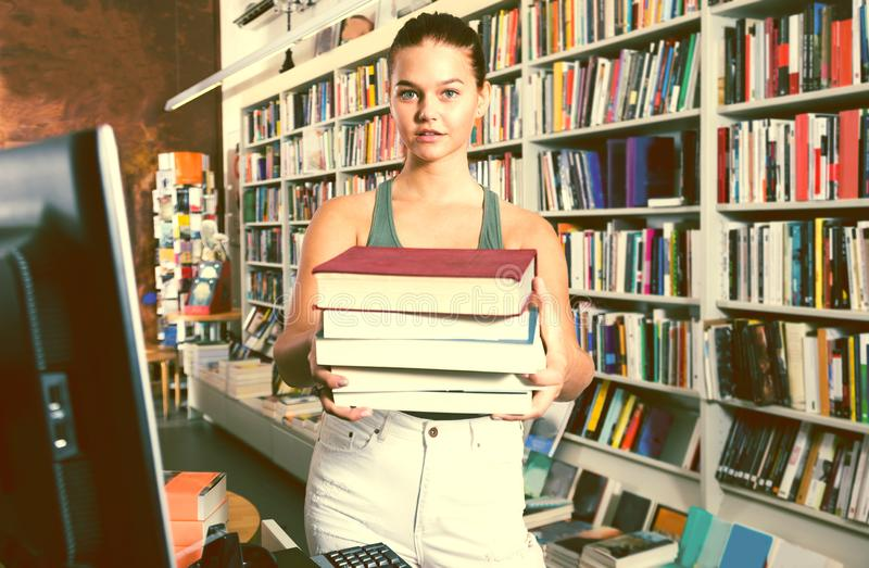 Girl holding a stack of books in a bookstore. Brunete girl holding a stack of books in a bookstore royalty free stock photography