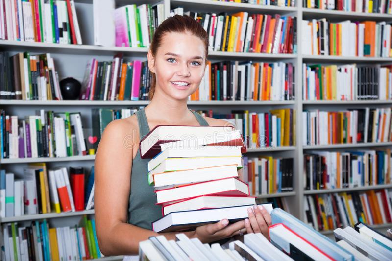 Brunete meisje koos heel wat boeken in universitaire bibliotheek stock foto