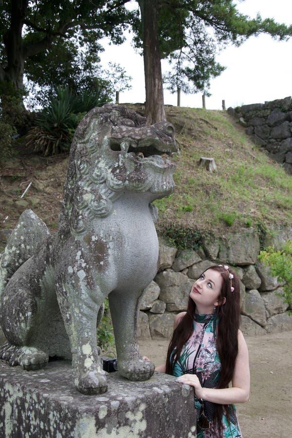 Brunetka hipisa caucasian dziewczyna podziwia antyczną uszkadzającą Japońską statuę zdjęcie royalty free