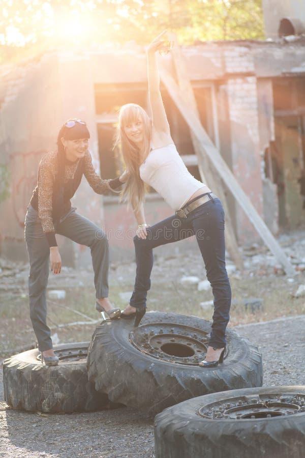 Brunetka i blondynka pozuje stać na gigancie męczymy outdoors fotografia stock