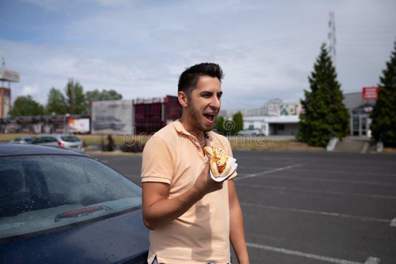 Brunetka mężczyzny łasowania hot dog w parking obrazy royalty free