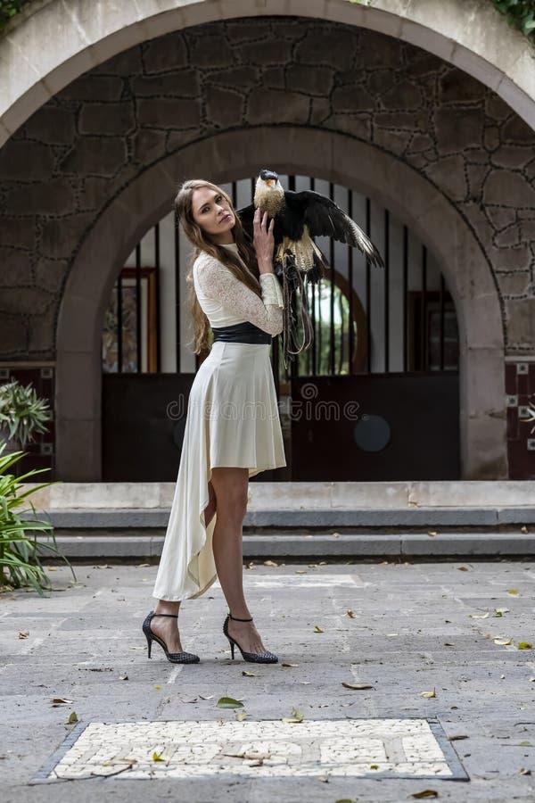 Brunetka modela Urocze Latynoskie pozy Outdoors Z Caracara ptakiem Przy hacjendy zdjęcie stock