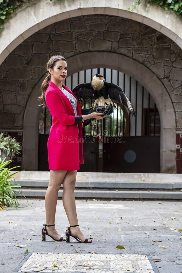 Brunetka modela Urocze Latynoskie pozy Outdoors Z Caracara ptakiem Przy hacjendy zdjęcie royalty free
