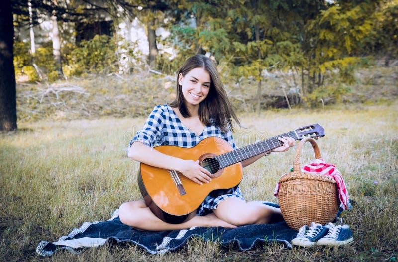 Brunetka ono uśmiecha się przy kamerą podczas gdy bawić się klasyczną gitarę fotografia stock