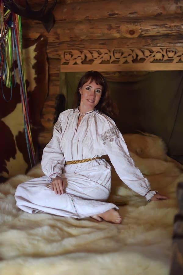 Brunetka w białej bieliźnianej staromodnej koszula z broderią siedzi na średniowiecznym łóżku zdjęcia stock