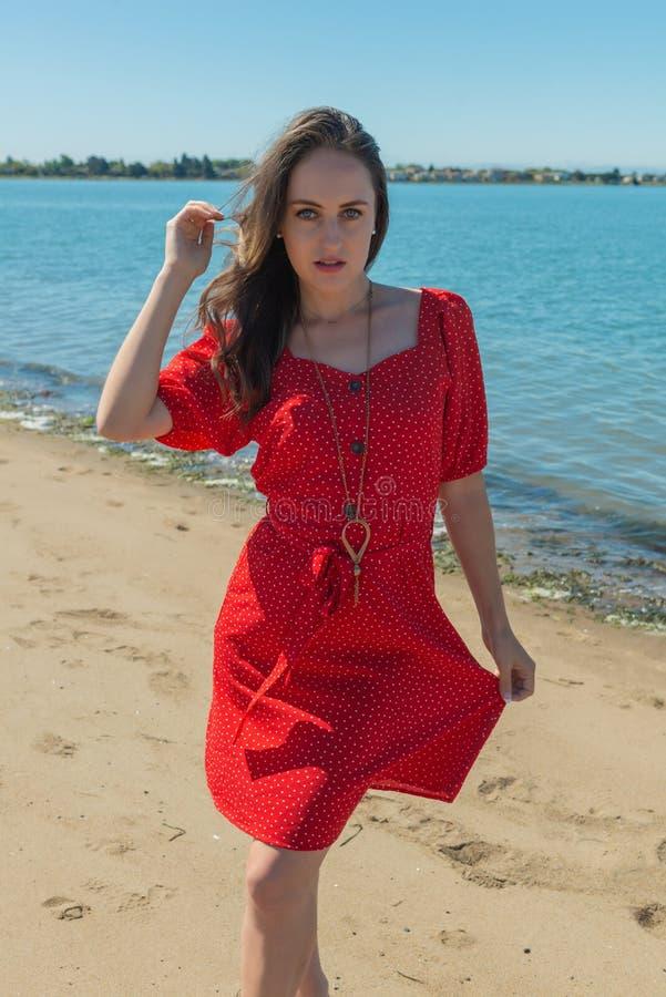 Brunetka w czerwieni na plaży obrazy royalty free