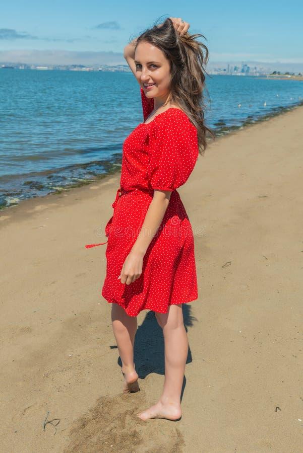 Brunetka w czerwieni na plaży zdjęcie royalty free