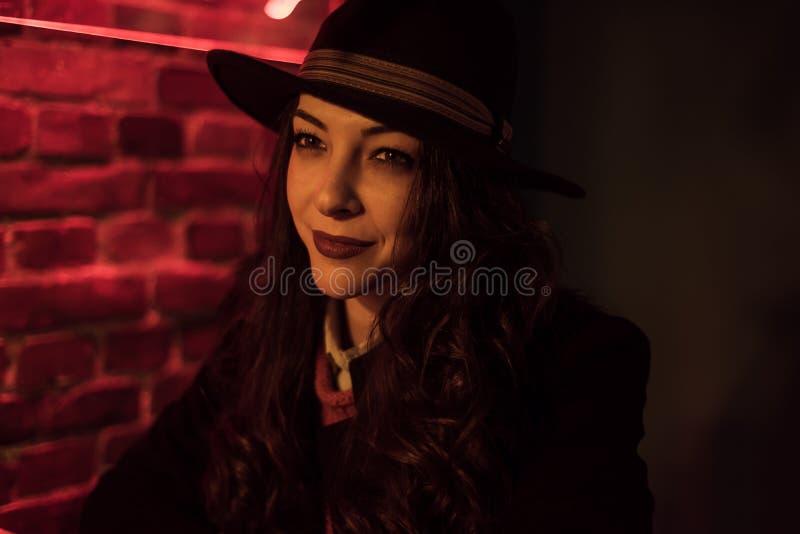 Brunetka z czarnym kapeluszem w barze zdjęcia royalty free