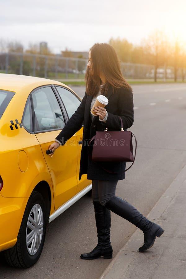Brunetka z długie włosy, opensing drzwi żółty taxi, zdjęcie stock