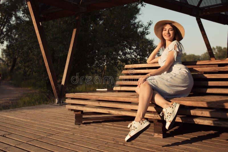 Brunetka z szkłami siedzi na parkowej ławce Zmierzchu światło, wieczór przypadkowej sukni kobiety potomstwa zdjęcie royalty free