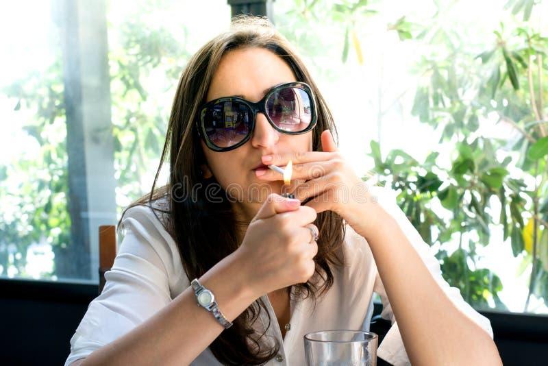 Brunetka zaświeca papieros, mieć dym zdjęcia royalty free