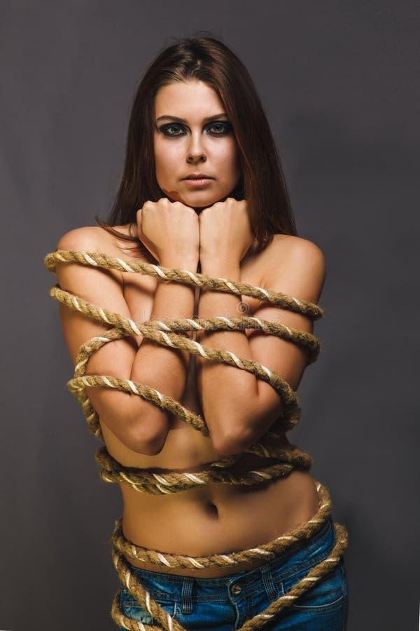 Brunetka zakładnik, zmonopolizowana kobieta odskakuje z linowym więźniem w cajgu fotografia royalty free