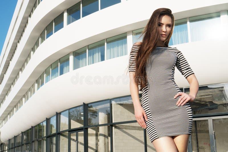 Brunetki Azjatycka kobieta jest ubranym paskującą smokingową pozycję przed białym budynkiem w mieście zdjęcie stock