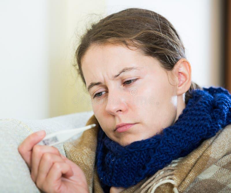 Brunetki choroba z febrą pod koc w domowym wnętrzu obraz royalty free