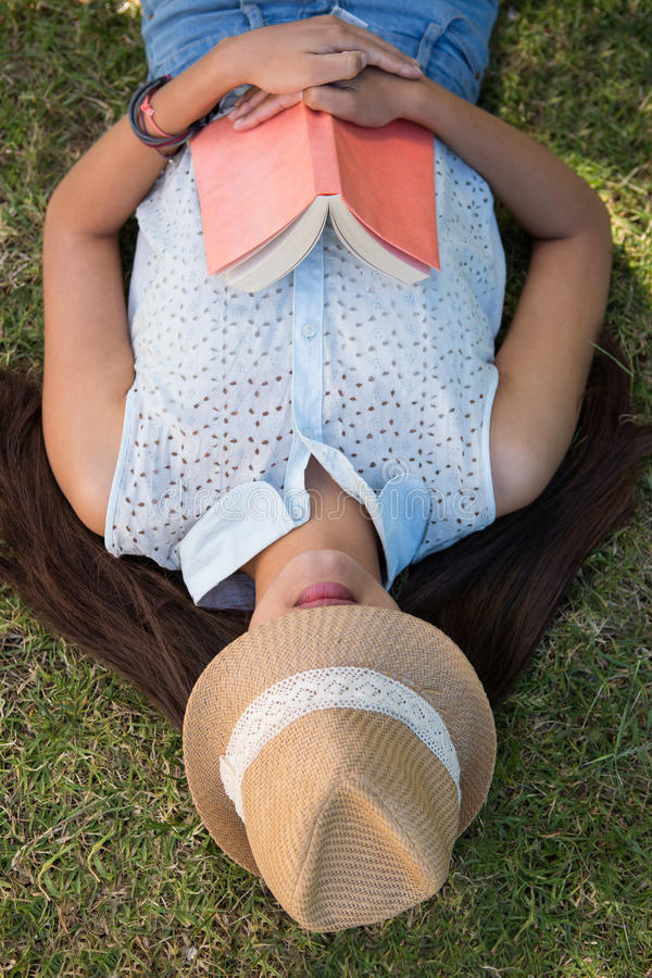 Brunetki drzemanie w parku z książką obraz stock