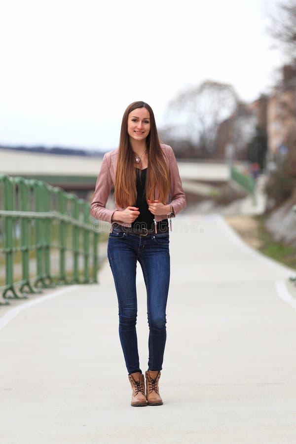 Brunetki dziewczyna jest ubranym skórzaną kurtkę, niebieskich dżinsy i buty, obrazy stock