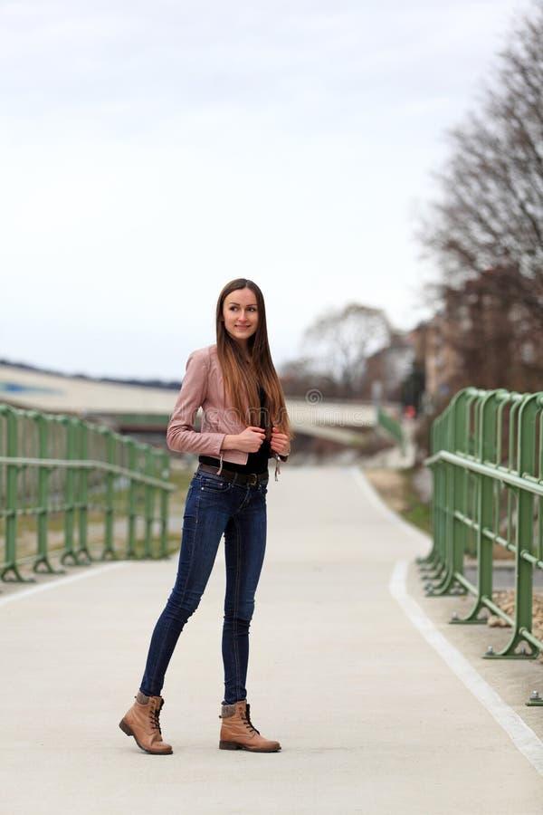 Brunetki dziewczyna jest ubranym skórzaną kurtkę, niebieskich dżinsy i buty, fotografia royalty free