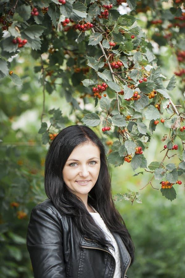Brunetki dziewczyna ono uśmiecha się na rowan drzewa tle zdjęcie stock