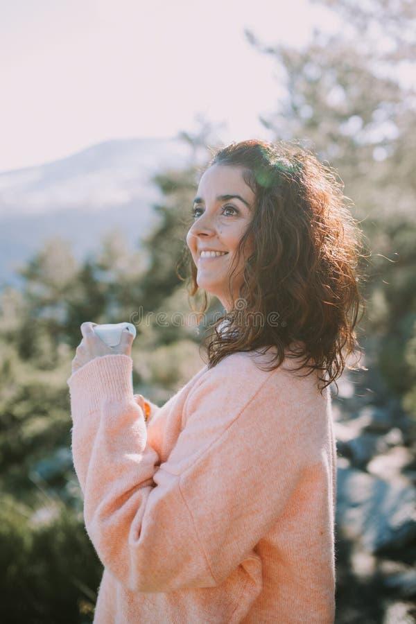 Brunetki dziewczyna ono uśmiecha się szczęśliwie gdy chwyta butelkę woda i spojrzenia przy pięknym krajobrazem przed ona fotografia royalty free
