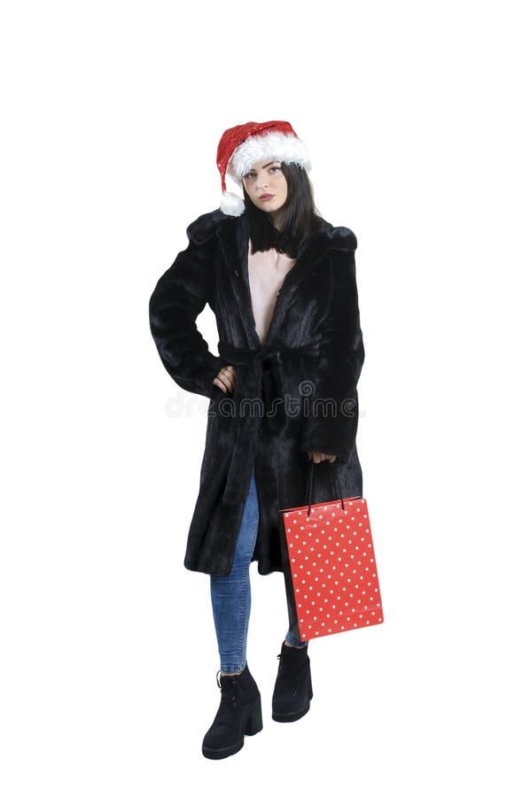 Brunetki dziewczyna w czarnym futerku, stylowy żakiet w Santa kapeluszu na odosobnionym tło portrecie obrazy royalty free