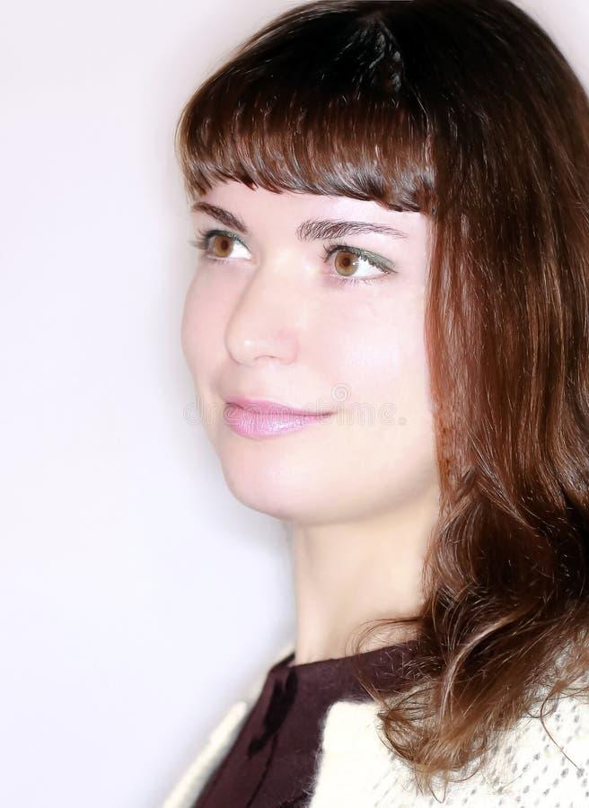 Brunetki dziewczyna w profilowy uśmiechniętym i patrzeć naprzód obrazy royalty free