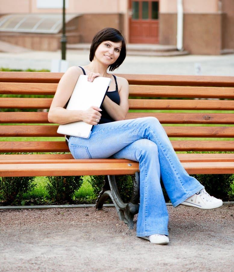 Brunetki dziewczyny obsiadanie na słonecznym dniu na ławce w parku z zdjęcie royalty free