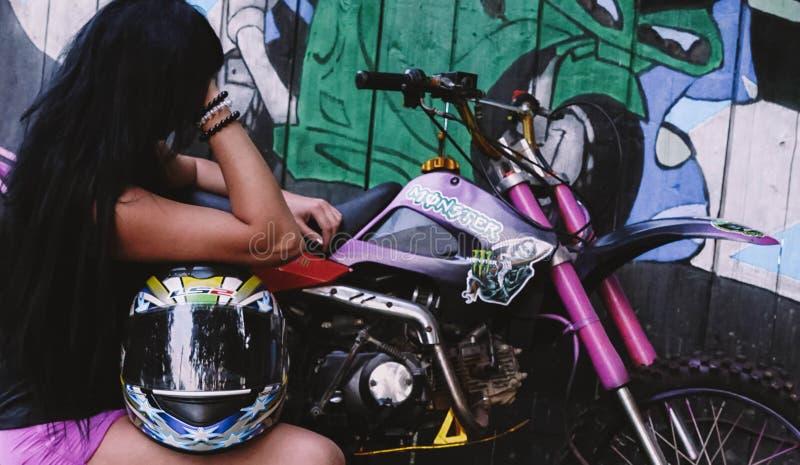 Brunetki dziewczyny obsiadanie przy mieniem i motocyklem hełm zdjęcia stock
