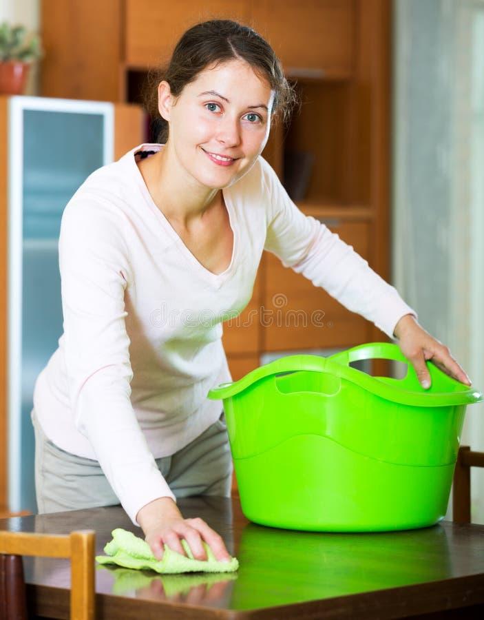 Brunetki dziewczyny okurzania meble w domu obraz stock