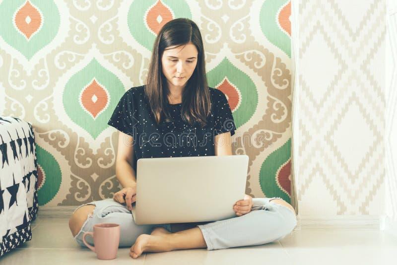 Brunetki freelancer obsiadanie na podłodze w pokoju studiuje strony internetowe w laptopie zdjęcie royalty free