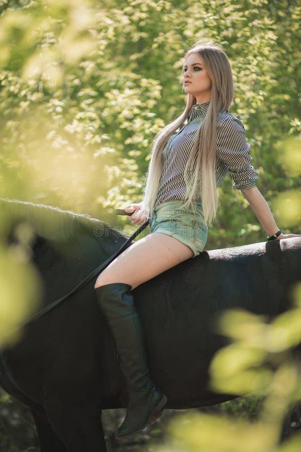 Brunetki kobieta jedzie ciemnego konia przy lato zieleni lasem obrazy royalty free