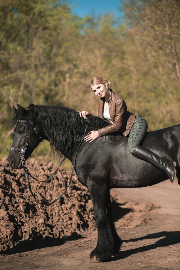 Brunetki kobieta jedzie ciemnego konia przy lato zieleni lasem fotografia royalty free