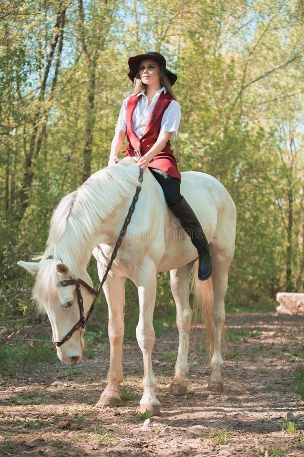 Brunetki kobieta jedzie ciemnego konia przy lato zieleni lasem zdjęcia stock