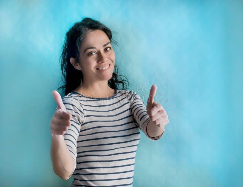 Brunetki kobieta nad odosobnionym tłem robi szczęśliwym aprobatom gestykuluje z rękami obraz royalty free