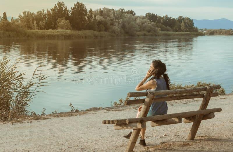 Brunetki kobieta opowiada z jej telefonem komórkowym przed piękną rzeką obraz royalty free