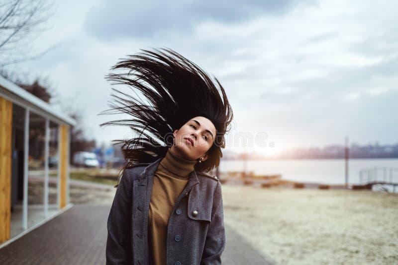 Brunetki kobieta plenerowa z dmuchaniem - w górę włosy zdjęcie stock