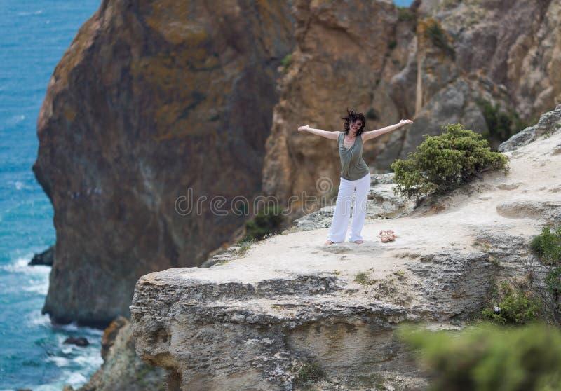 Brunetki kobieta pozuje na falezie z rękami szeroko rozpościerać zdjęcie stock