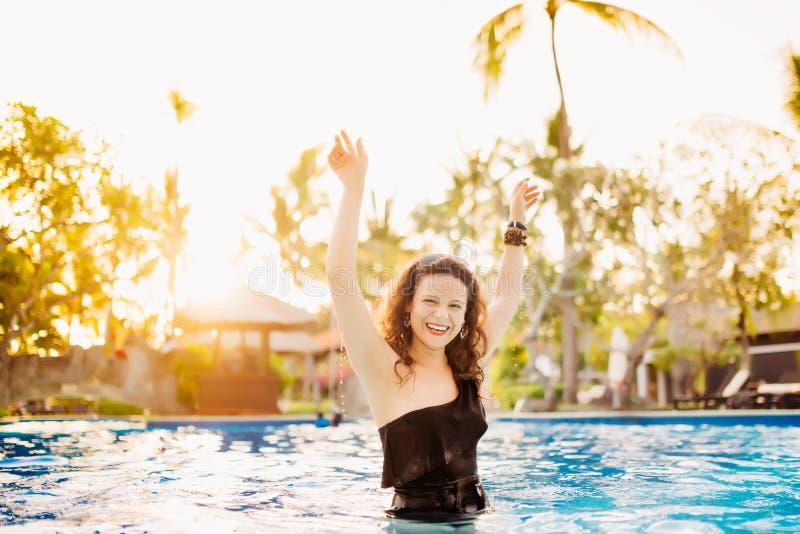 Brunetki kobieta robi wodnemu pluśnięciu w seksownym bikini przy basenem Szczupła dysponowana skórnicza kobieta ma zabawę w basen obraz royalty free