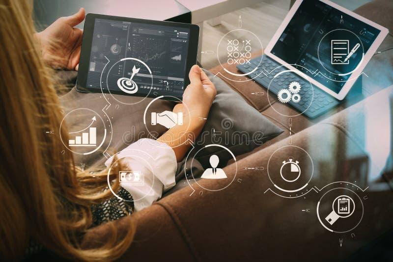 brunetki kobieta używa cyfrowego talet i laptop na kanapie ja obrazy stock