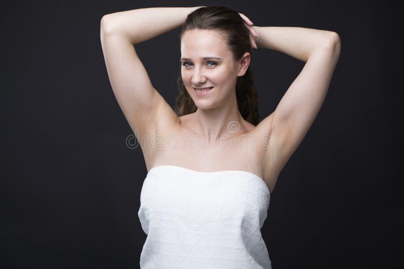 Brunetki kobieta w białym ręczniku z twój rękami up obraz stock