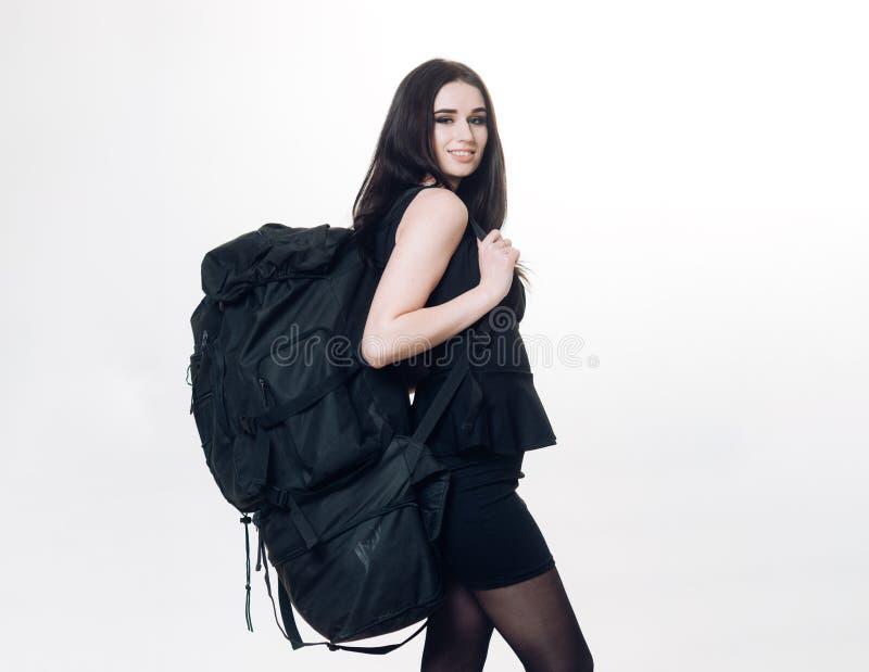 Brunetki kobieta w krótki smokingowy ono uśmiecha się podczas gdy niosący ogromnego czarnego plecaka na białym tle zdjęcie royalty free