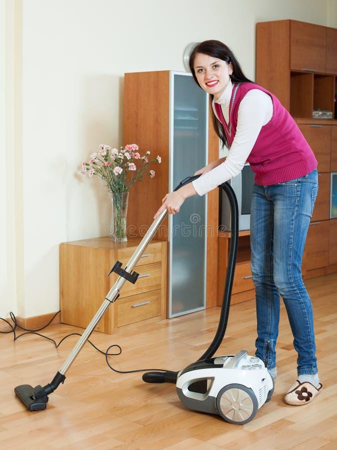 Brunetki kobiety cleaning z próżniowym cleaner obrazy stock