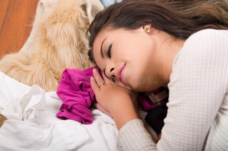 Brunetki kobiety lying on the beach na stosie ubrania ono uśmiecha się i pojawiać się śpi, garderoba zakupy mody pojęcie zdjęcie stock
