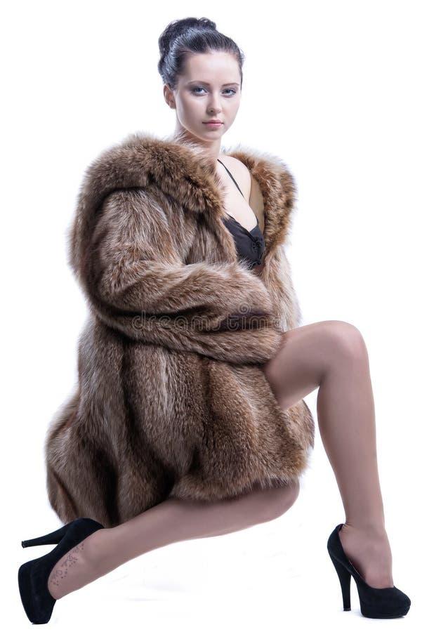 Młody brunetki obsiadanie w pozie jest ubranym galanteryjnego futerkowego żakiet i pięty obraz royalty free