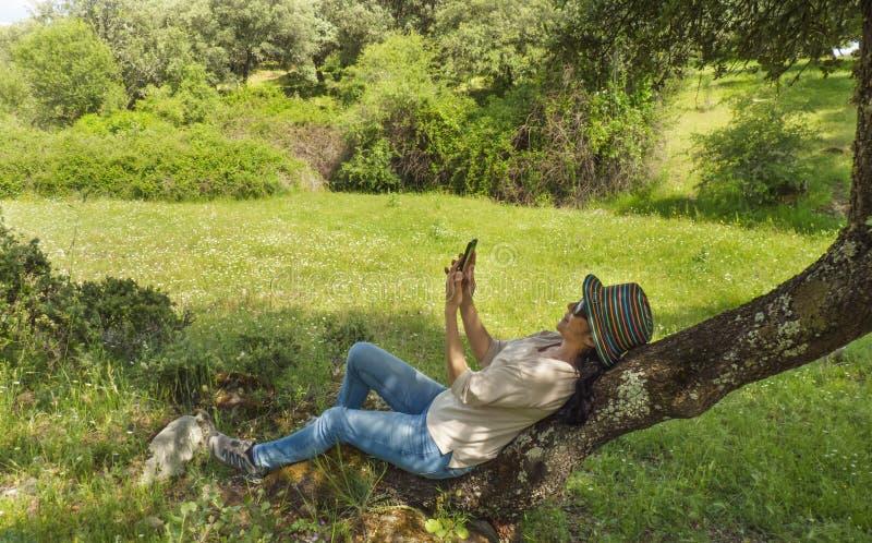 Brunetki kobiety obsiadanie na drzewie, patrzeje jej telefon komórkowego obrazy royalty free
