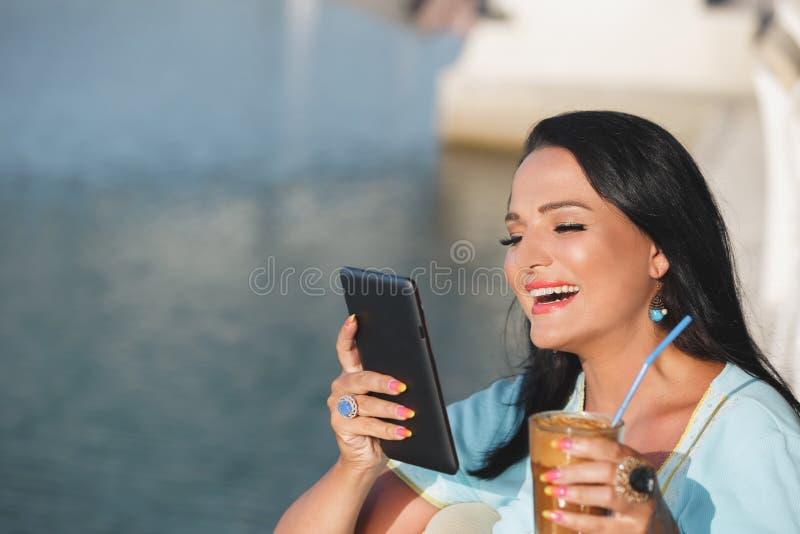 Brunetki kobiety obsiadanie w nadmorski kawiarni podczas gdy mieć kawowego i używać pastylka komputer fotografia royalty free
