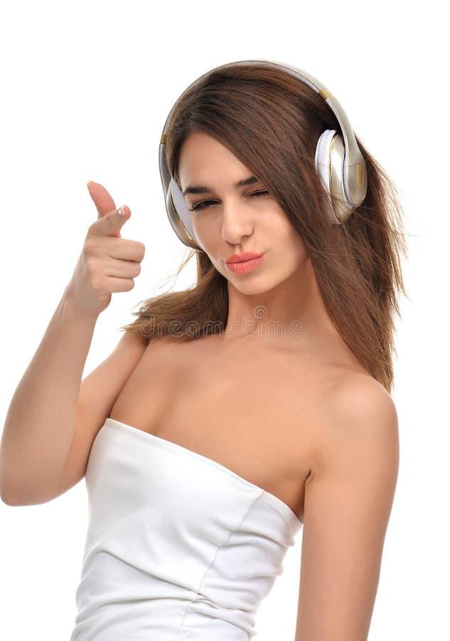 Brunetki kobiety słuchanie i cieszyć się muzyka w złocistych hełmofonach obraz stock