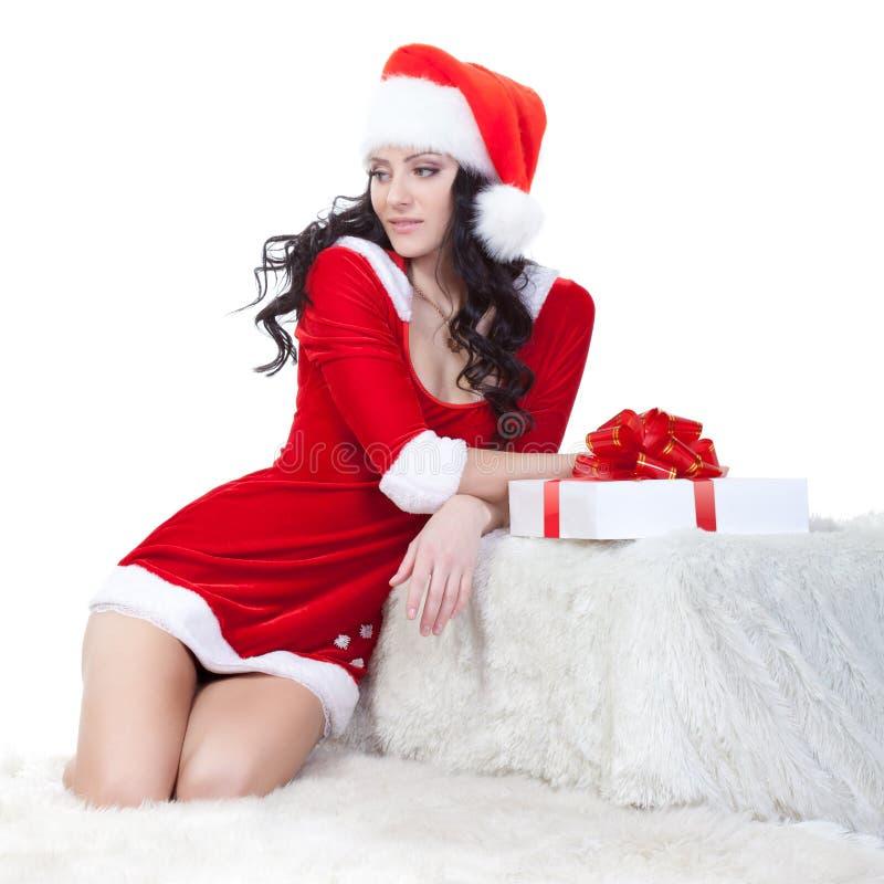brunetki kostiumowa Santa siedząca kanapa obraz stock