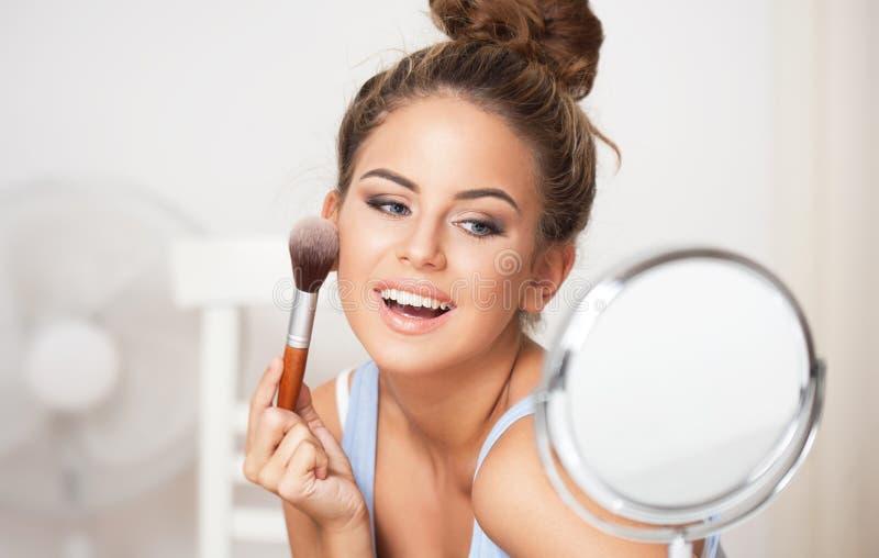 Brunetki piękno robi jej makeup zdjęcie stock