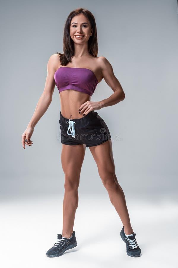 Brunetki sprawności fizycznej seksowna dziewczyna w sport odzieży z perfect ciałem w studiu pozuje przed trenować set Duży łup obrazy stock