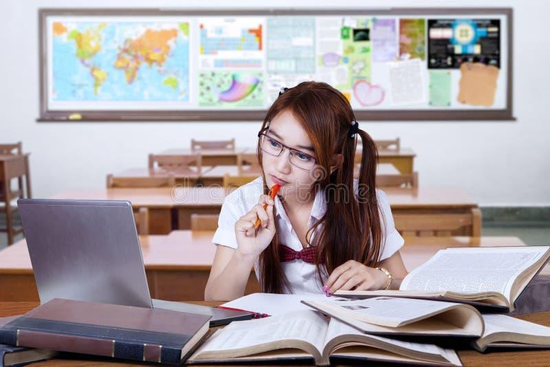 Brunetki studencki studiowanie na biurku w klasie fotografia royalty free